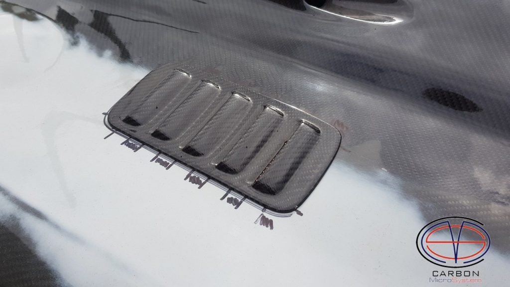 Carbon inserts in hood